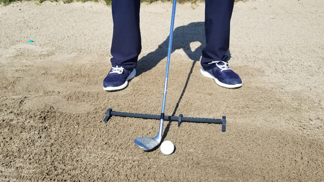Man hitting out of a sand bunker with Rimer Ball Position Trainer