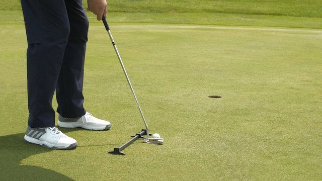 Man putting with Rimer Ball Position Trainer